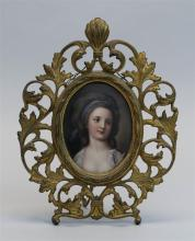 FRAMED PAINTED PORCELAIN PLAQUE Depicts a woman with a blue ribbon in her hair. In a floral gilt-painted pot metal frame. Oval 5