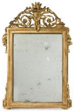 CARVED AND GILT MIRROR Openwork pediment with basket of flowers and scrolling foliage. Old, possibly period mirror glass. Frame with...