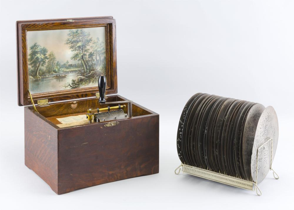 REGINA MUSIC BOX Numbered 66848. Oak case with lithographed panel depicting a moonlit landscape affixed to interior of lid. Includes...