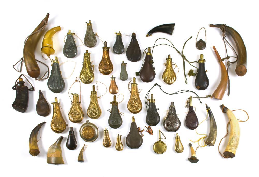 FORTY POWDER FLASKS AND HORNS Twelve powder horns, five leather powder flasks and 23 copper, tin and brass powder flasks. Also inclu...