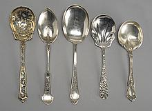 FIVE AMERICAN SILVER SERVING SPOONS An enamel and gold-washed pierced berry spoon, three serving spoons and a large pea spoon by var...