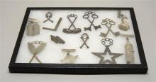 TWELVE ASSORTED FRATERNAL JEWELS Two in the form of crossed keys, others in the form of the Bible, crossed swords, crossed gavels, a...