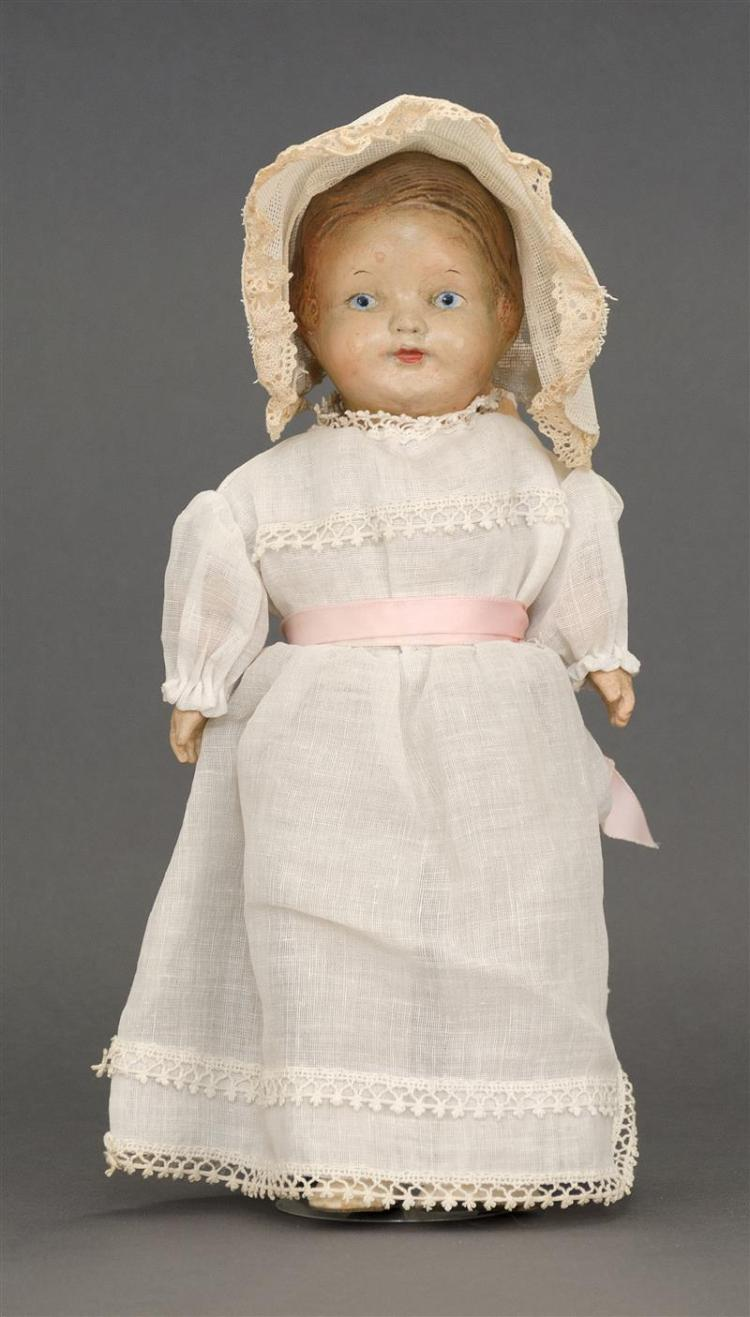 COMPOSITION DOLL Painted features include brown hair and blue eyes. Kid body with composition hands. Dressed in a white lace dress a...