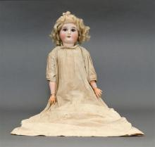 GERMAN BISQUE-HEAD DOLL With blonde wig, blue sleep eyes and open mouth. Composition ball-jointed body. Dressed in a white christeni...