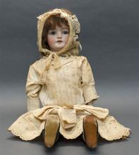 SIMON & HALBIG #1079 BISQUE-HEAD DOLL With brown wig, blue sleep eyes and open mouth. Composition ball-jointed body. Dressed in a wh...