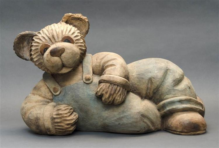 CARVED WOODEN FIGURE OF A RECLINING BEAR Under a natural finish. Bear is wearing a pair of overalls. Height 12