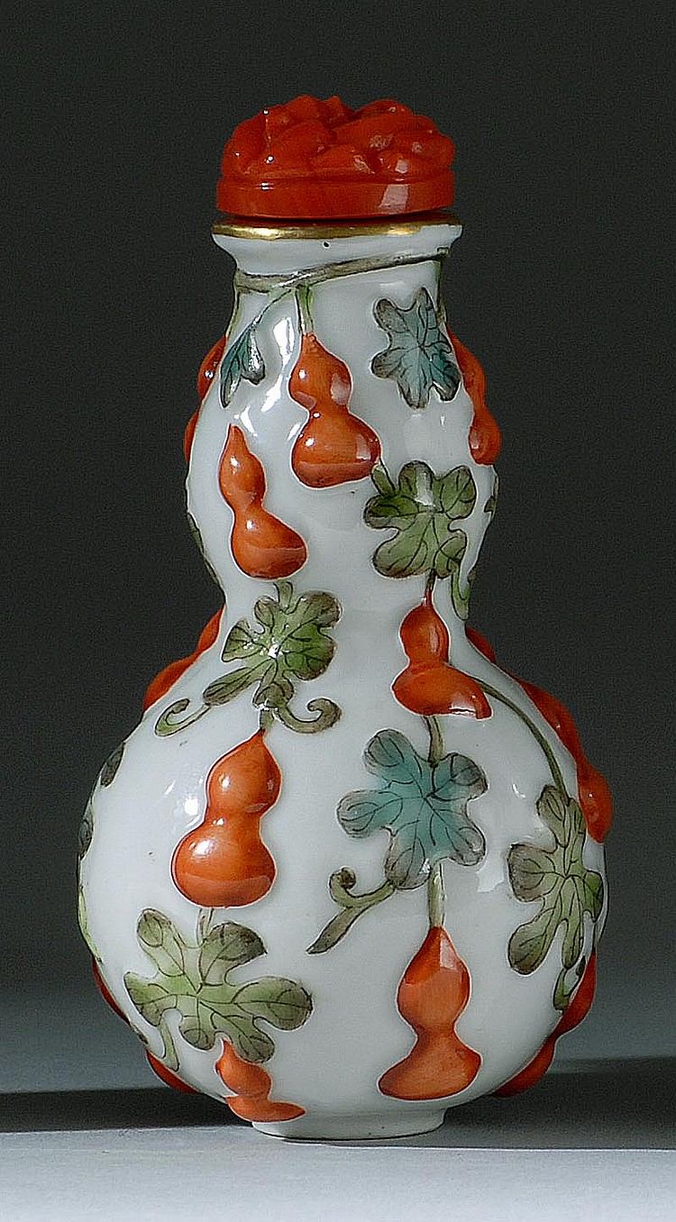 MOLDED PORCELAIN SNUFF BOTTLE In double gourd form with coral-red and green relief gourd and vine design. Four-character Qianlong ma...