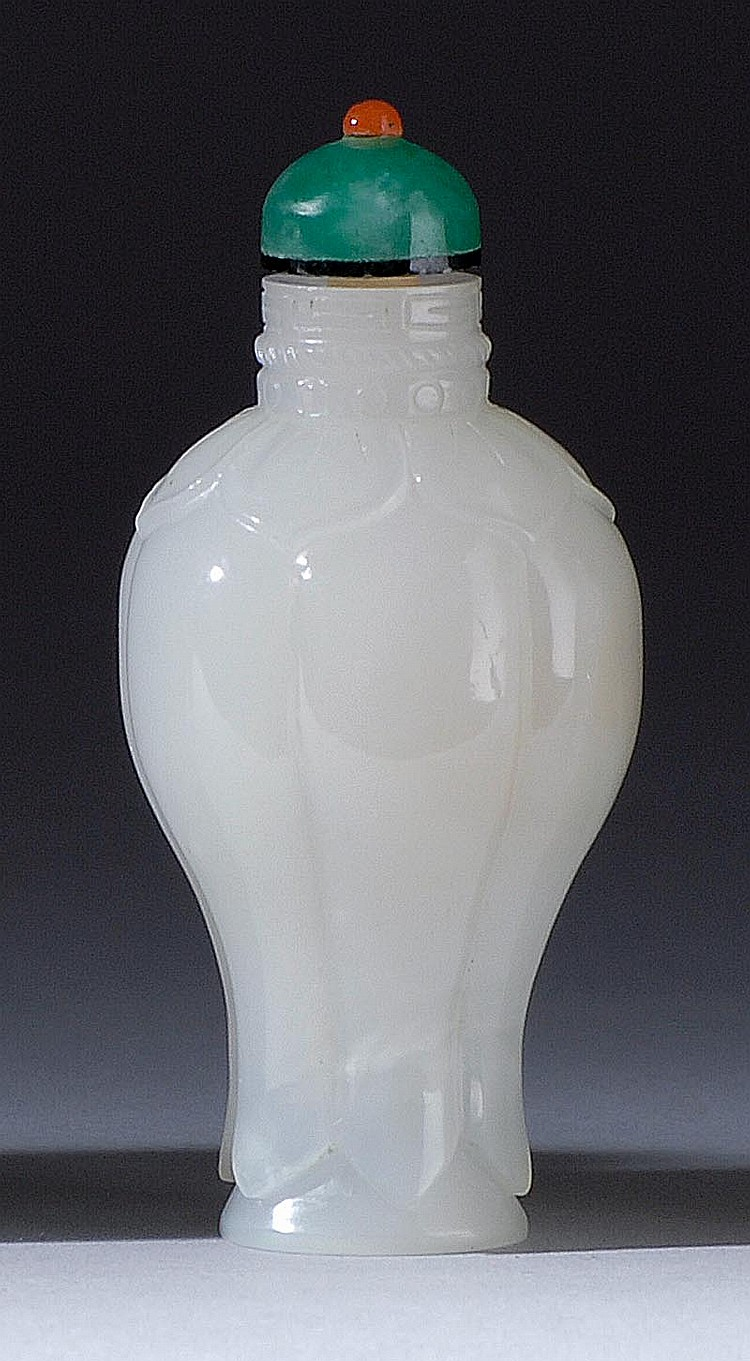 WHITE JADE SNUFF BOTTLE In six-lobed temple jar form with lappet carving. Height 2