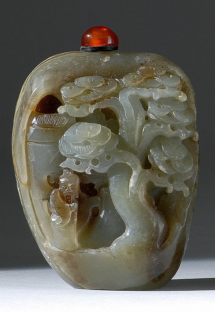 CELADON JADE SNUFF BOTTLE In pebble form with relief depiction of a sage beneath a pine tree. Height 3