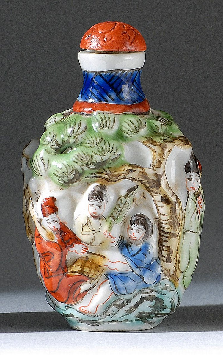 MOLDED PORCELAIN SNUFF BOTTLE In spade shape with relief figural landscape design. Four-character mark on base. Height 2¼