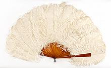 WHITE OSTRICH FEATHER AND CELLULOID FAN Beautiful white ostrich feathers extend from amber-colored celluloid sticks and guards. Simp.