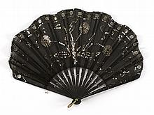 GAUZE AND BLACK WOOD FONTAGE FAN With applied floral design in silver sequins on the leaf. Scattered piqué on sticks and guards. Met...