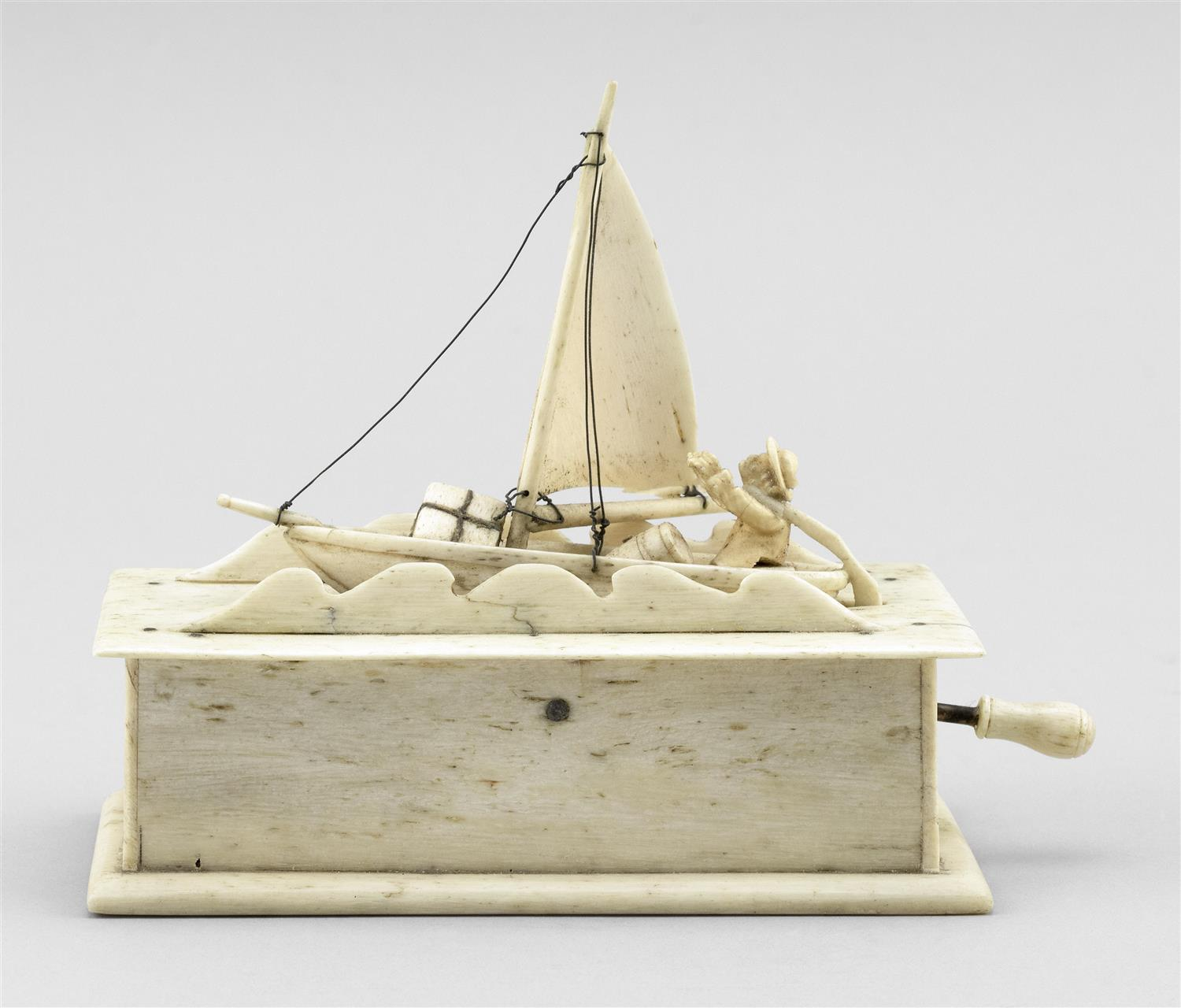 WHALEBONE SAILBOAT TOY Manned sailboat set into a box with handle at side that rocks the boat. Finely detailed with long bowsprit, b...