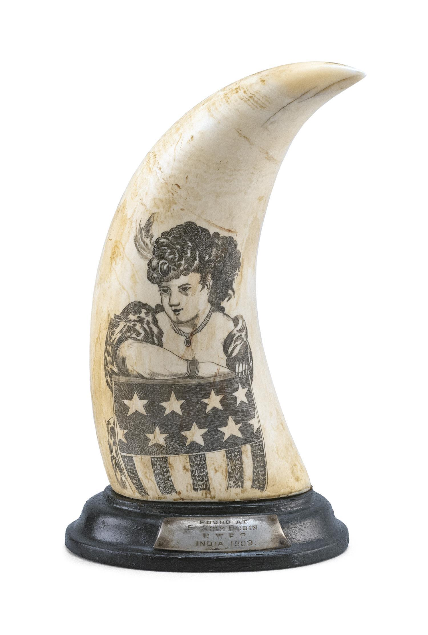 """SCRIMSHAW WHALE'S TOOTH DEPICTING THE CIRCUS PERFORMER """"ZAZEL"""" """"Zazel"""", dressed in a low-cut gown, poses inside a barrel decorated a.."""