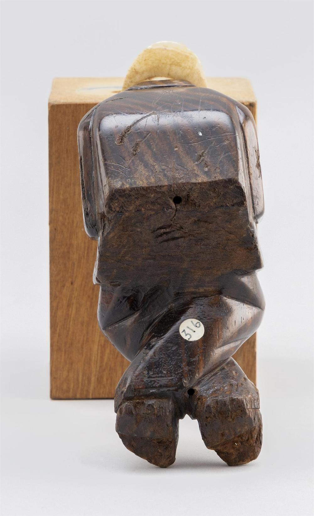 CARVED WHALE IVORY AND TROPICAL WOOD FIGURE OF A MAN A bearded man in a top hat, suit and tie, seated with his hands crossed over hi...