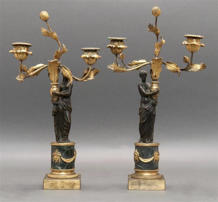 PAIR OF LOUIS-XV-STYLE FIGURAL BRONZE TWO-LIGHT CANDELABRA Both with gilt foliate stems and sconces issuing from an urn held by a st...