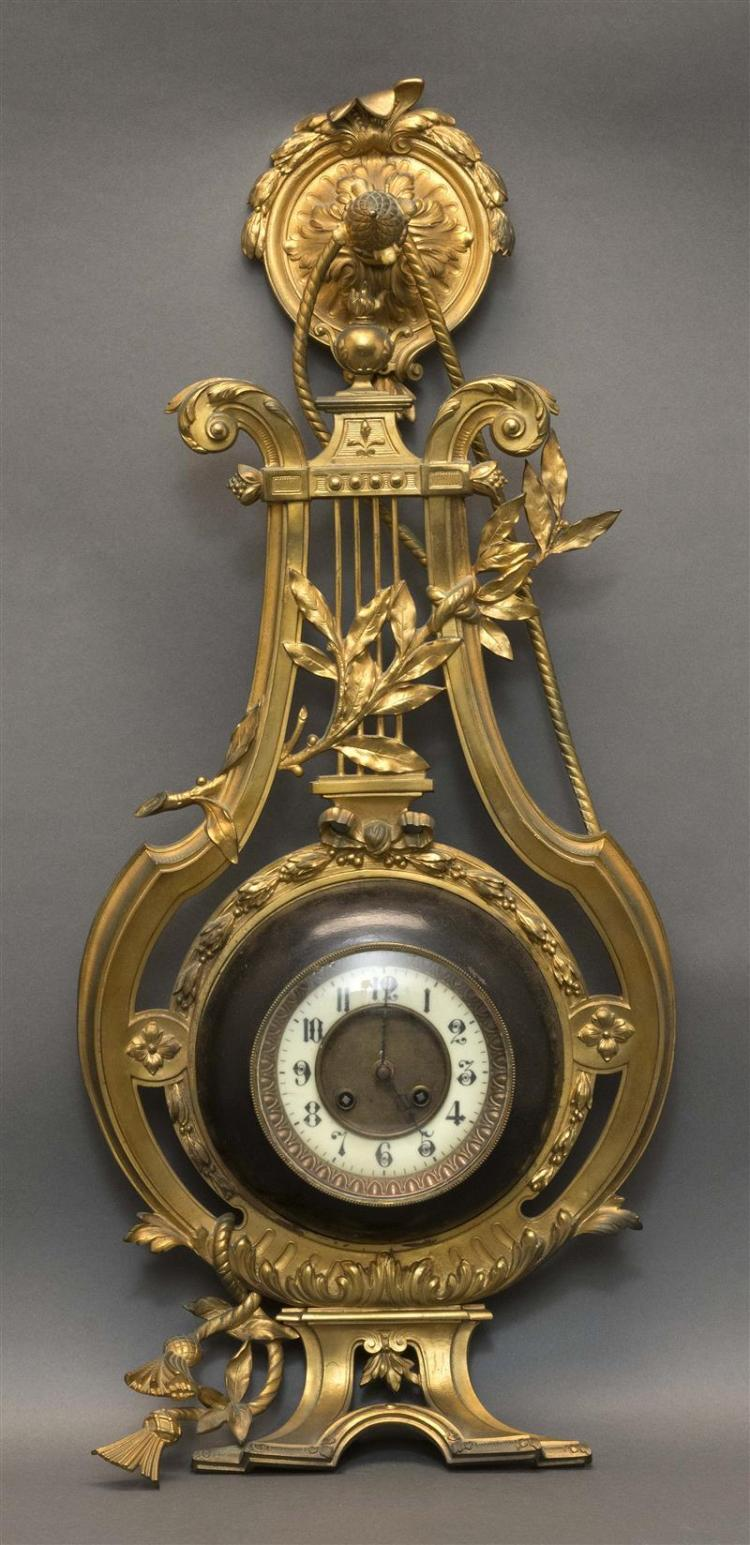 FRENCH GILT-BRONZE LYRE-FORM WALL CLOCK The openwork instrument adorned with foliage and tassels. Number ring with Arabic numerals....