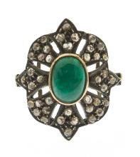 VICTORIAN BI-COLOR GOLD, EMERALD, AND DIAMOND RING The central emerald cabochon measuring 9 mm x 6.8 mm. x 3.6 mm. Surrounded by for...