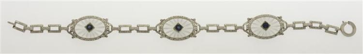 ART DECO WHITE GOLD, ROCK CRYSTAL, AND SAPPHIRE BRACELET Three oval medallions with cut starburst design with small central sapphire...