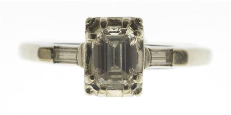 14KT WHITE GOLD AND DIAMOND SOLITAIRE RING The central emerald-cut diamond approx. 5.4 mm x 3.8 mm x 2.4 mm. Flanked by two small di...