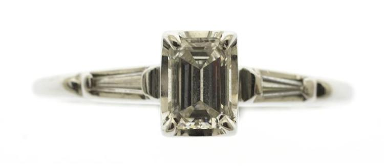 18KT WHITE GOLD AND DIAMOND SOLITAIRE RING The central emerald-cut diamond approx. 5.0 mm x 3.2 mm x 2.0 mm. Flanked by two small di...