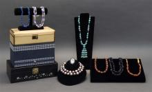 LARGE ASSORTMENT OF COSTUME JEWELRY Contained in three jewelry boxes. Includes: necklaces, rings, pins, and earrings in plastic, met...