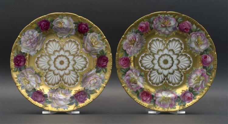 TWO CAULDON HAND-PAINTED PORCELAIN CABINET PLATES Each with central foliate design surrounded by heavy gilt border decorated with ro...