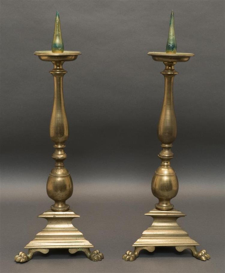 PAIR OF CONTINENTAL BRASS PRICKET STICKS Turned vasiform stems on triangle bases with paw feet. Heights 19.5