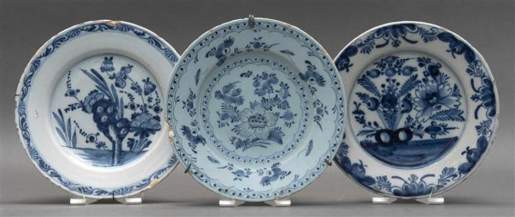 THREE BLUE AND WHITE ENGLISH DELFT PLATES In floral designs. Diameters approximately 9