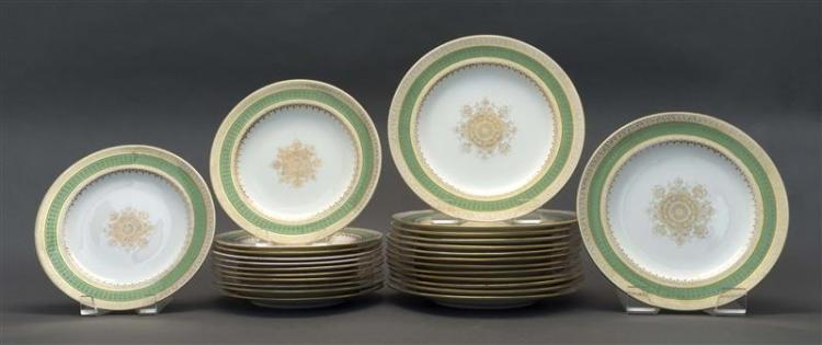 TWENTY-SIX WEDGWOOD PORCELAIN PLATES Pattern x2525. Borders with band of kelly green and stylized gilt designs. Central gilt medalli...