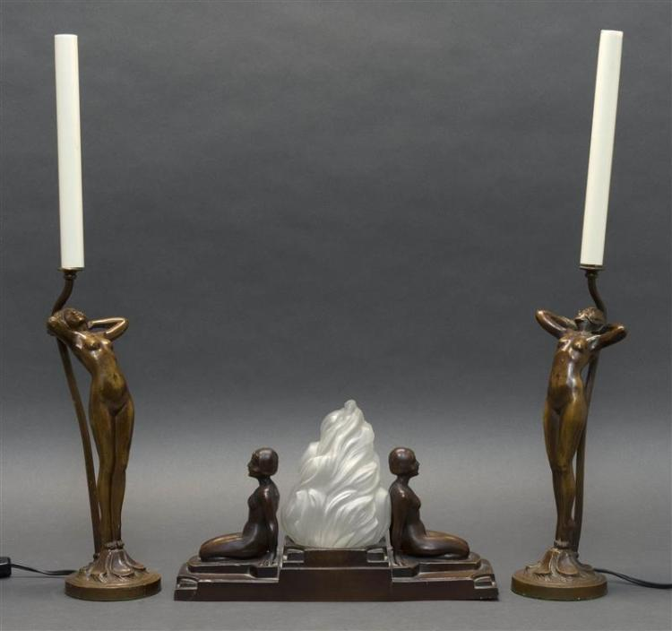 THREE PIECES OF METAL ART DECO FIGURAL LIGHTING A desk lamp with kneeling nudes flanking a frosted glass shade on a stepped base, he...