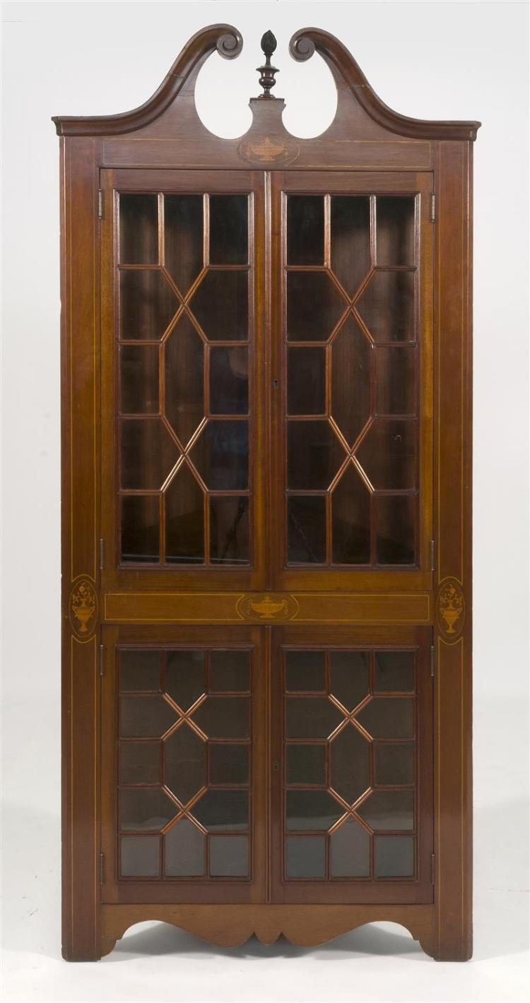 EDWARDIAN MAHOGANY-VENEER CORNER CABINET In one piece. With broken arch pediment and single finial above two sets of through-mullion...