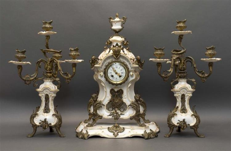 PORCELAIN THREE-PIECE MANTEL GARNITURE SET Includes a clock with plateau and a pair of candelabra, all in white porcelain with gilt...