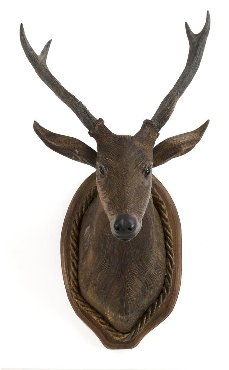 BLACK FOREST CARVED WOOD BUST OF A STAG Inset with actual antlers and German glass eyes. Mounted on a wood shield-form plaque with r...