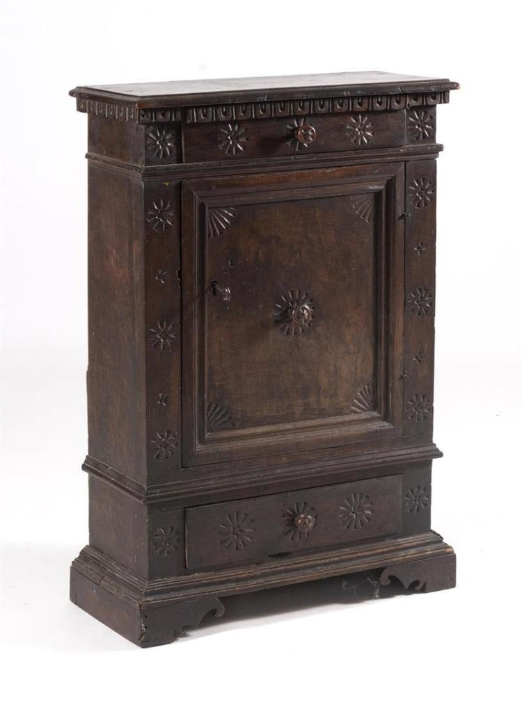 CONTINENTAL CUPBOARD In walnut with carved snowflake decoration throughout. Shaped cornice over an upper and lower drawer and a medi...