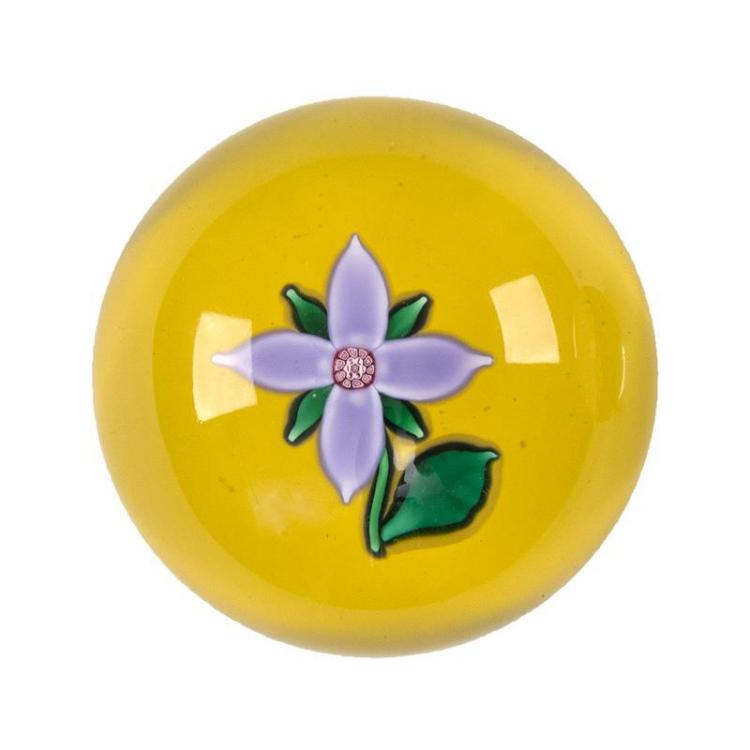 CONTEMPORARY ST. LOUIS FLORAL PAPERWEIGHT Lavender-blossomed flower with green leaves on a yellow ground. Acid signature on bottom....