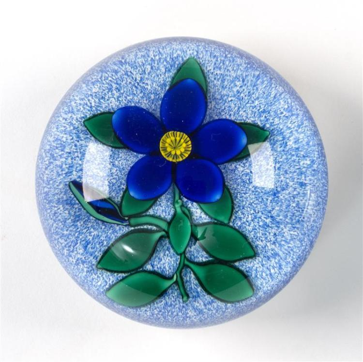 CHARLES KAZIAN FLORAL PAPERWEIGHT Blue flower with green leaves on a white and blue speckled ground. Signed