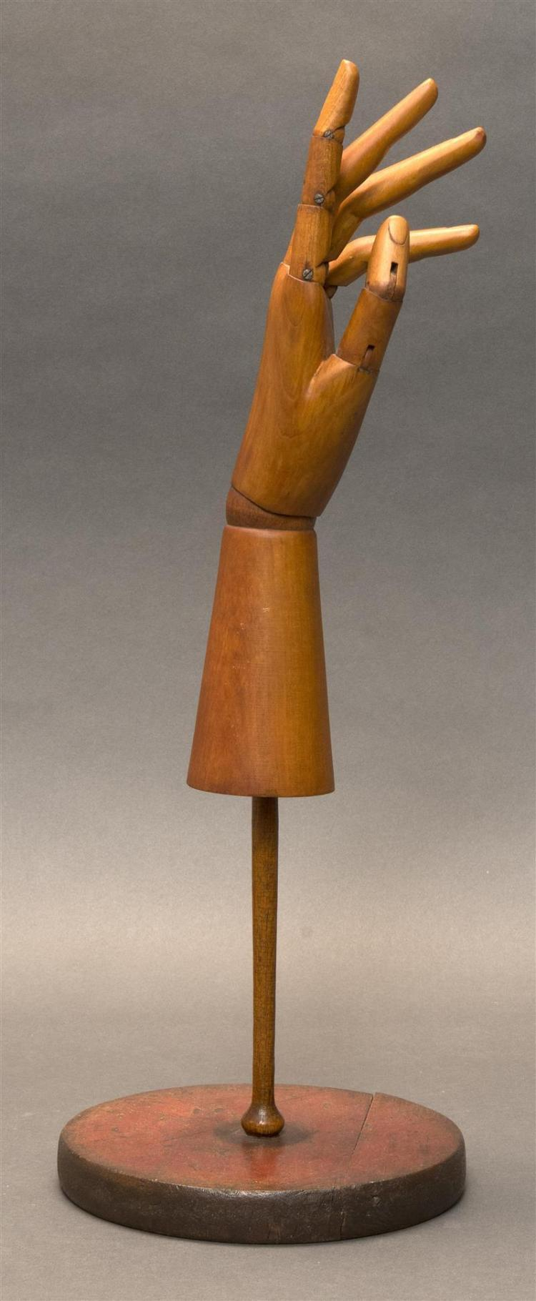 ARTICULATED ARTIST'S WOOD MODEL OF A HAND Fully poseable and on a conical base. Stamped on underside