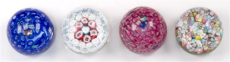 FOUR GLASS PAPERWEIGHTS Two millefiori and two in broken cane designs. Diameters approximately 3