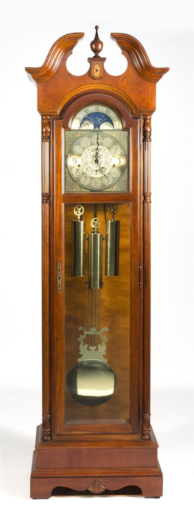 HOWARD MILLER CLOCK In walnut veneer with broken arch top. Includes weights and pendulum. Height 79.5