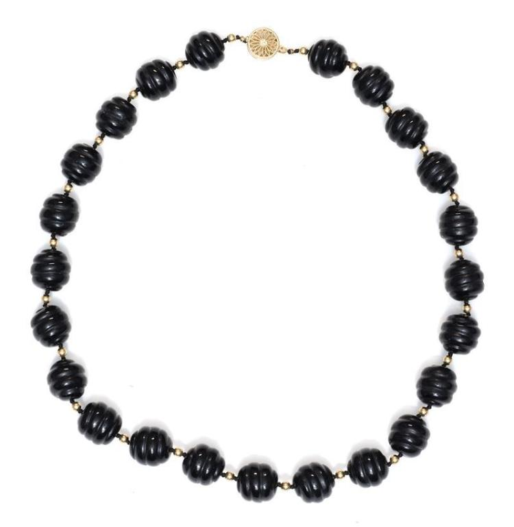 BLACK CORAL AND 14KT GOLD BEAD NECKLACE With 14kt gold clasp. Coral beads carved with spiral design. Length overall 20.75