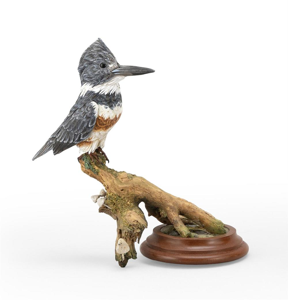 "FRANK ADAMO MINIATURE BELTED KINGFISHER Mounted on an oval driftwood base adorned with mushroom carvings. Signed on underside ""F. Ad..."