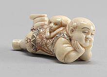 POLYCHROME IVORY NETSUKE In the form of a sleeping child with a puppy lying on his back. Length 2