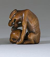 WOOD NETSUKE In the form of a wolf seated with a human skull. Wolf with inlaid eyes. Height 2