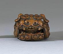WOOD NETSUKE In the form of a lion mask with movable jaw. Signed