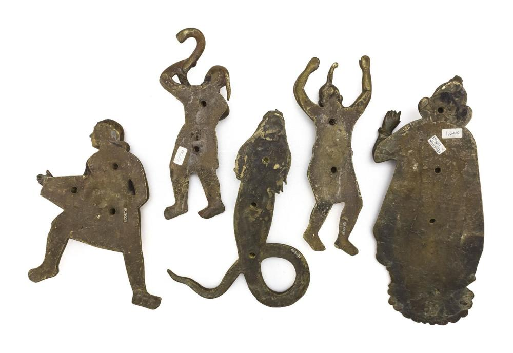 FIVE INDIAN BRASS FIGURAL PLAQUES In the forms of a man with a basket, height 8.5