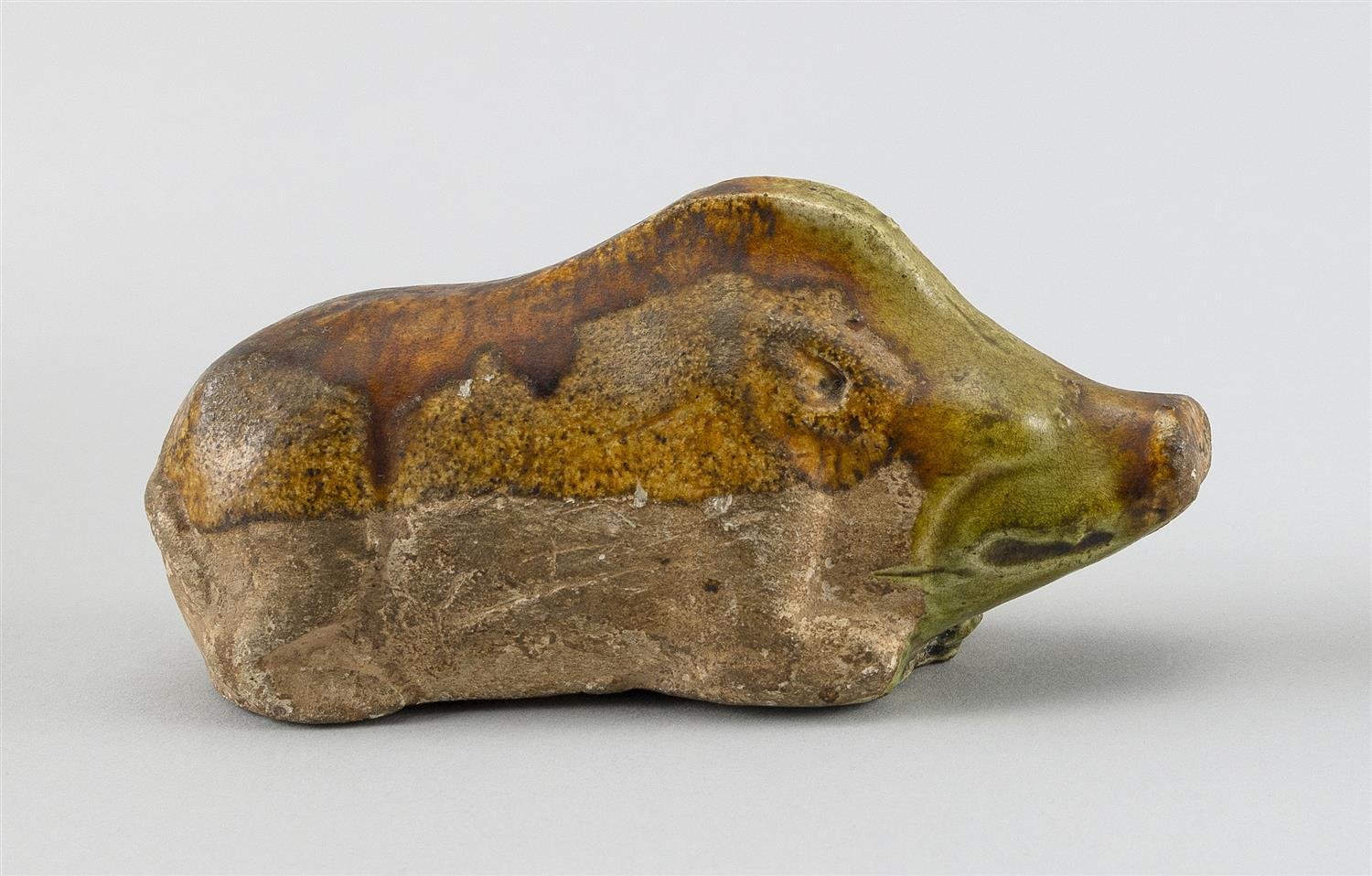 """CHINESE SPINACH AND EGG GLAZE POTTERY FIGURE OF A RECLINING BOAR Length 4.5"""". Provenance: The Symmes / Shiro Kuma Collection."""
