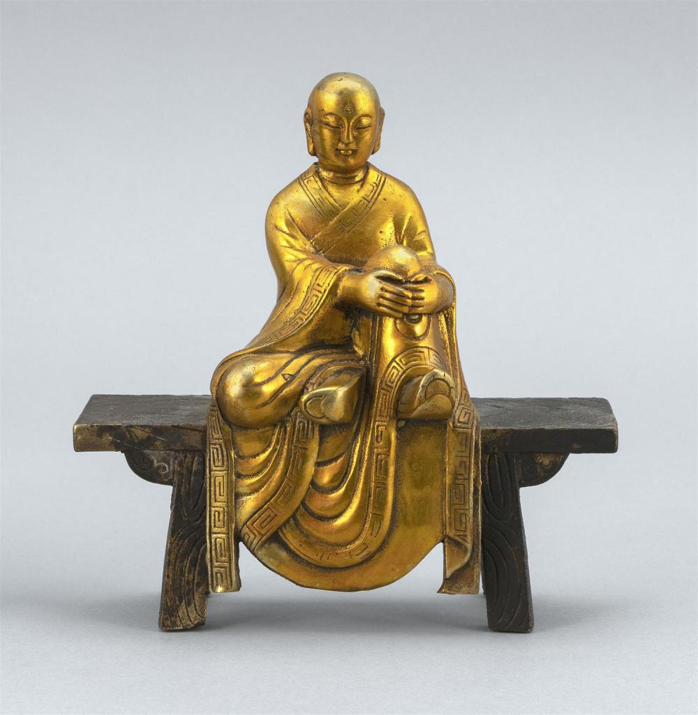 "GILT BRONZE FIGURE OF BUDDHA Seated on an altar bench. Height 6"". Length 5""."