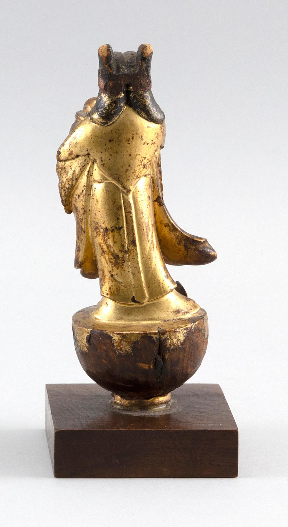 CHINESE GILT WOODEN POLE FINIAL In the form of an acolyte standing on a lotus pod and holding an offering. Height 6