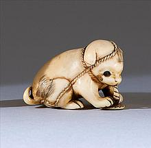 IVORY NETSUKE In the form of a puppy with inlaid eyes chewing on a sandal. Length 1.5